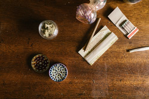 Weed Paraphernalias on Top of Wooden Table