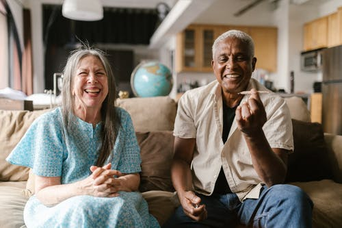 Happy Elderly Couple Sitting on a Beige Sofa