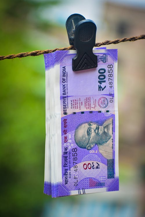 Close Up Photo of Indian Bank Notes Clipped on Rope