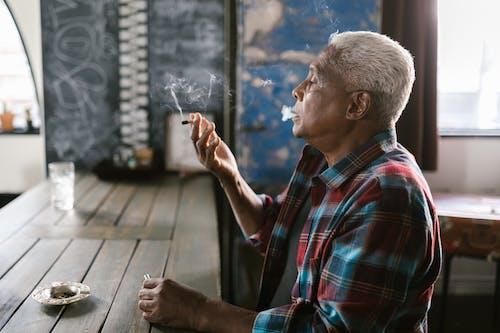 Side View Photo of Elderly Man Smoking Pot