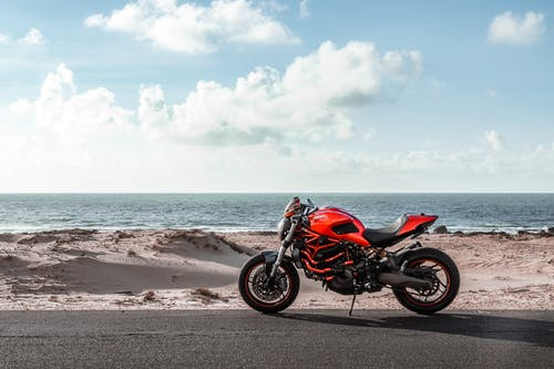 Red and Black Naked Motorcycle on Beach