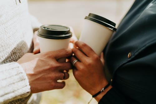Close-Up Shot of Two Persons Holding Cups of Beverages