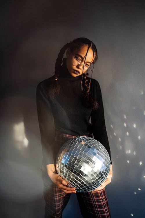 Woman in Black Long Sleeve Shirt Holding Disco Ball