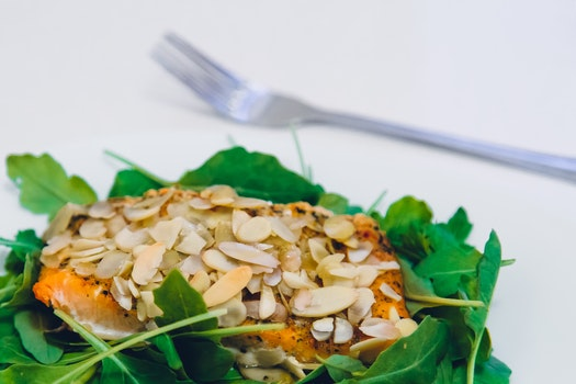 Green Leaf Covering Meat With Sesame Seeds With a Fork on the Side