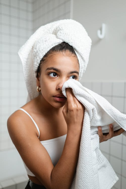 Woman in White Tank Top Wiping Her Face With Towel