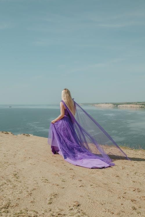 Woman in Purple Dress Standing on Beach