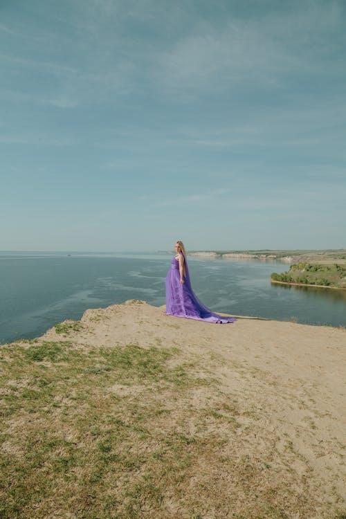Woman in Purple Dress Standing on Brown Rock Near Body of Water