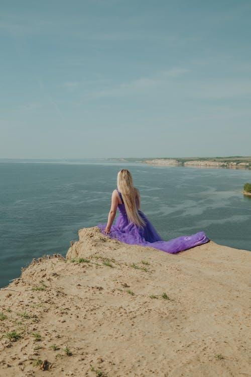 Woman in Purple Dress Sitting on Brown Rock Near Body of Water