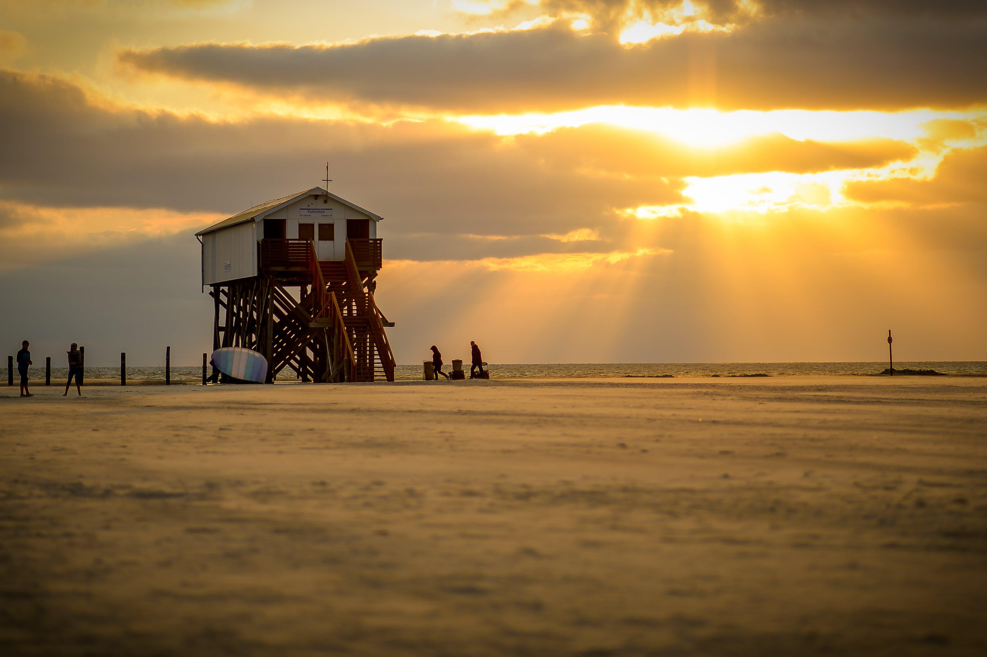 White Lifeguard House on Beach Taken Under White Clouds and Orange Sky