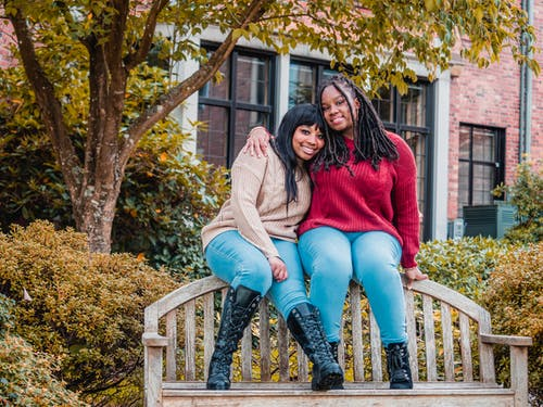 African American Ladies Sitting on Top of Wooden Bench