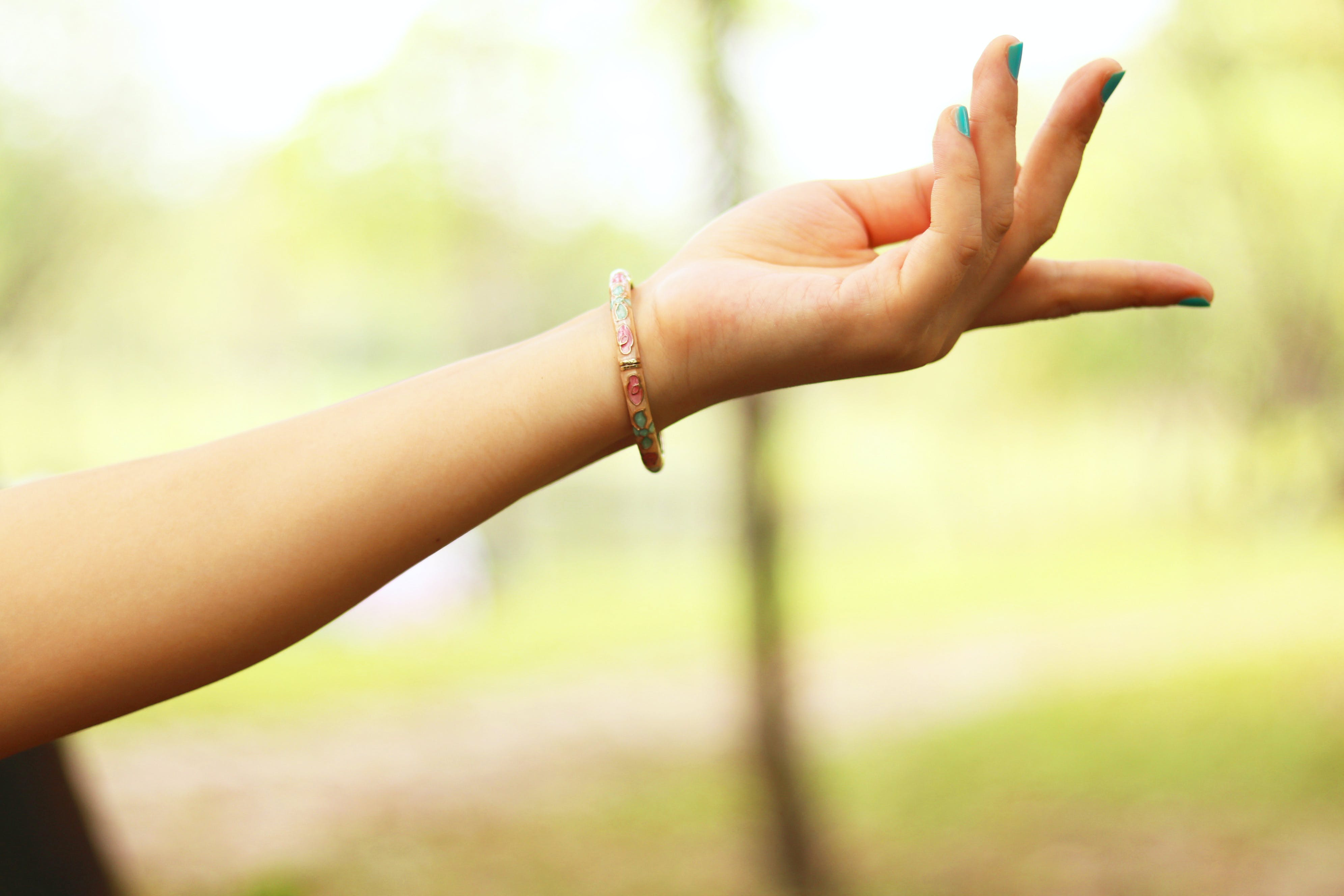 Close-Up Photography of Girl's Left Hand Wearing Bracelet