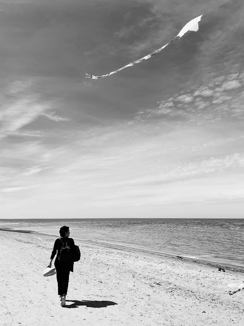 A Grayscale of a Woman Walking on a Beach