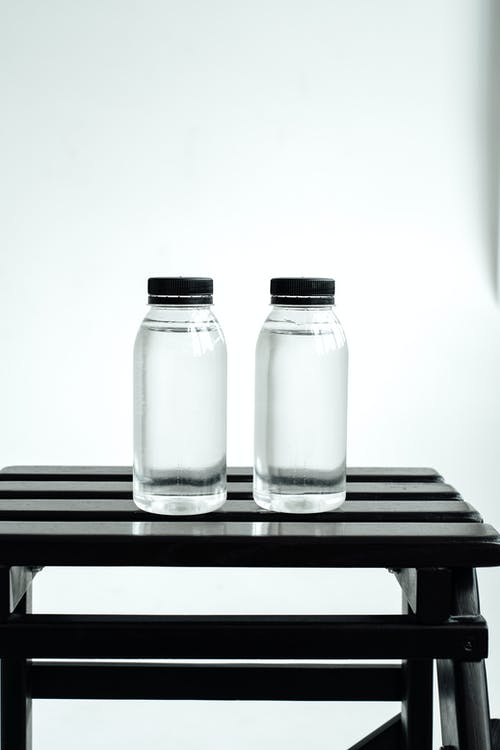 2 Clear Glass Bottles on Black Wooden Table