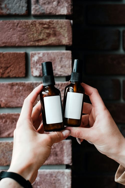 2 Brown Glass Bottles on Persons Hand