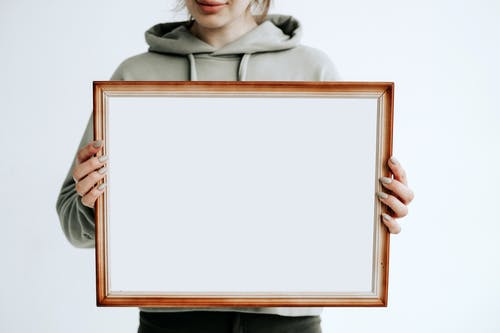 Woman in Gray Hoodie Holding Brown Wooden Frame