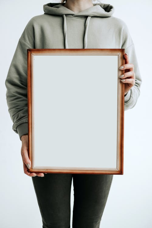 Person Holding White and Brown Frame