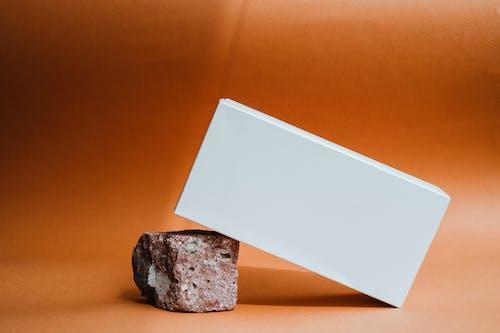 White Printer Paper on Brown Rock