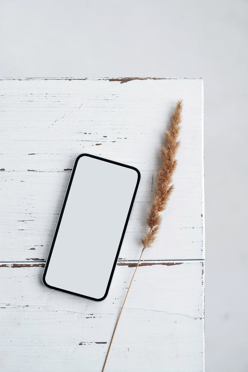 Black Mobile Phone on White Wooden Table