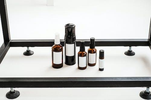 Black and White Bottles on White Table