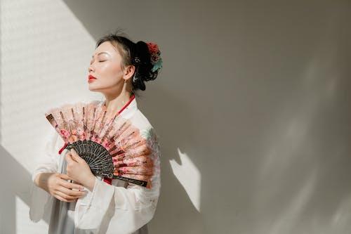 Woman in White Long Sleeve Dress Holding Hand Fan
