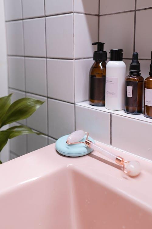 Brown and White Plastic Bottles on White Ceramic Sink