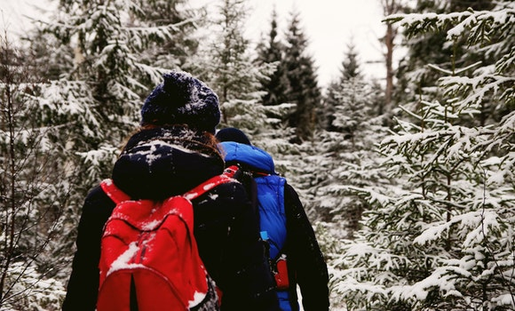 Two People Wearing Jacket And Red Backpack During Winter Season