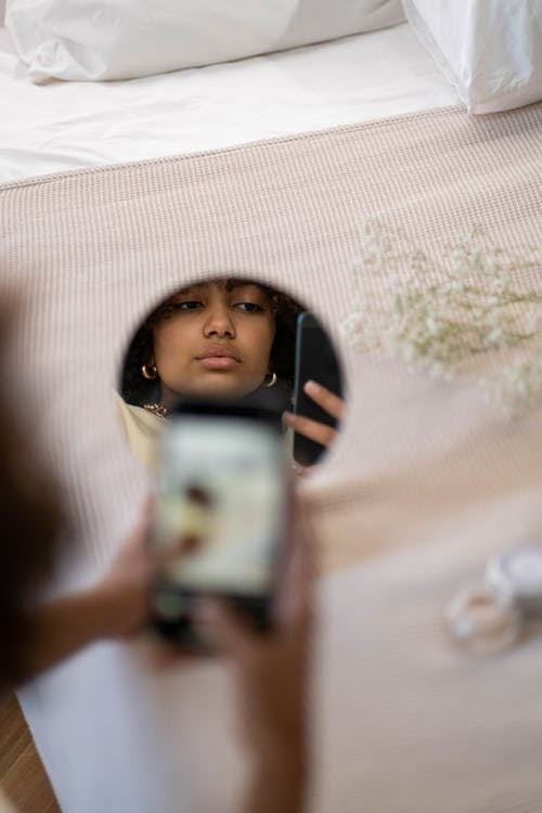 Reflection Of Woman Taking Selfie in Front of Mirror