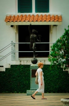 Woman Walking in Front Of Statue