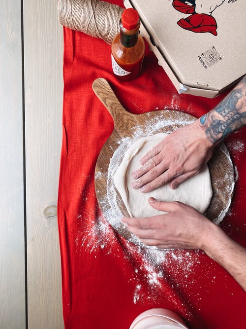 Person Holding White Powder on Red Textile