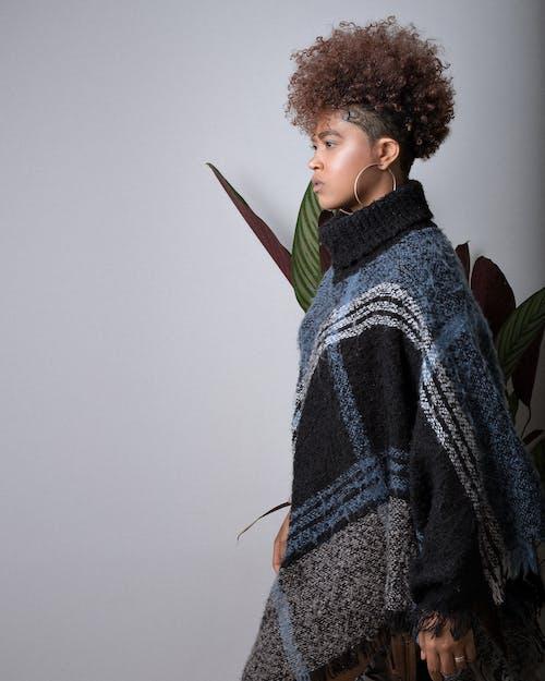 Stylish ethnic model in poncho on light background