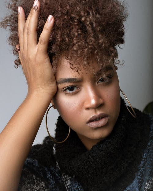 Stylish African American female with makeup and Afro hairstyle touching head while looking at camera on gray background