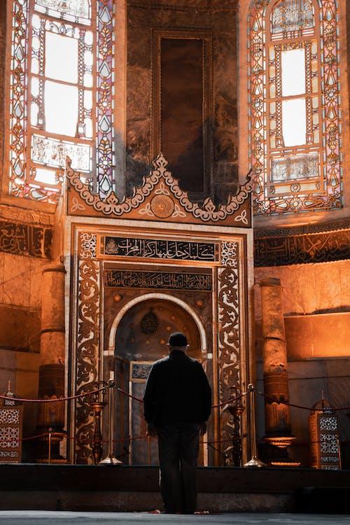 Man in Black Jacket Standing in Front of Brown Wooden Door