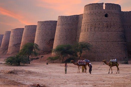 Dos hombres tirando de camellos marrones al lado de hito de formación de roca