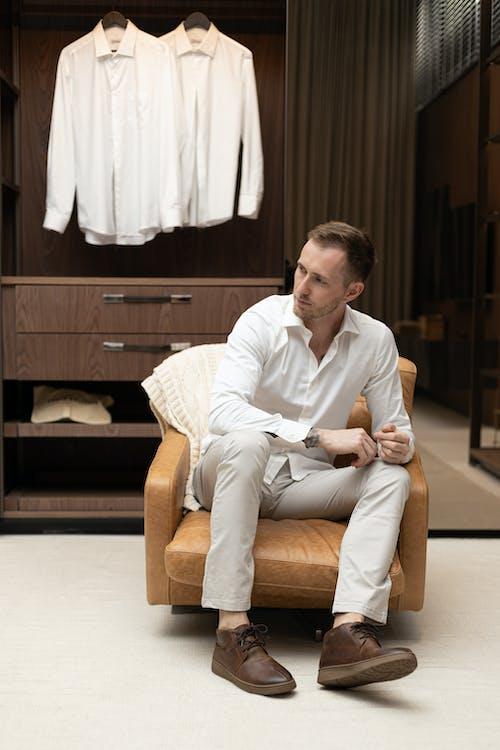 Man in White Dress Shirt Sitting on Brown Sofa Chair