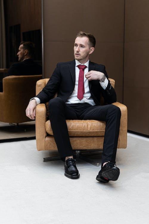 Man in Black Suit Sitting on Brown Sofa Chair