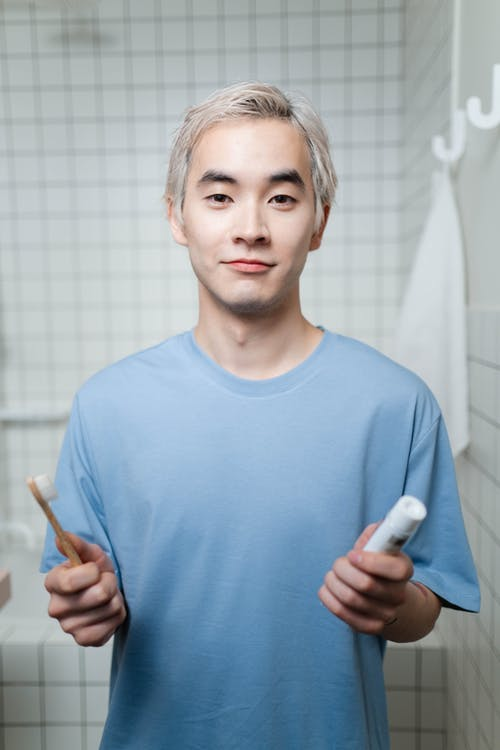 Man in Blue Crew Neck Shirt Holding A Toothbrush And Toothpaste