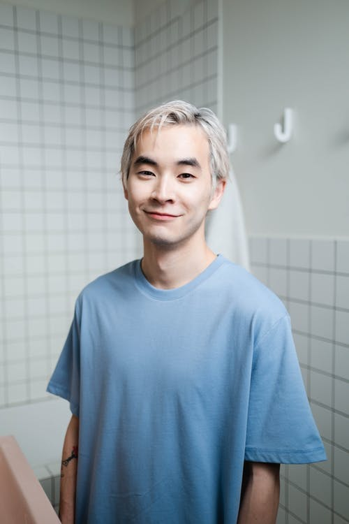 A Smiling Young Man in Blue Crew Neck T-shirt And Blonde Hair