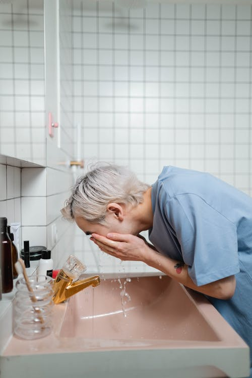 Man in Blue T-shirt Washing His Face