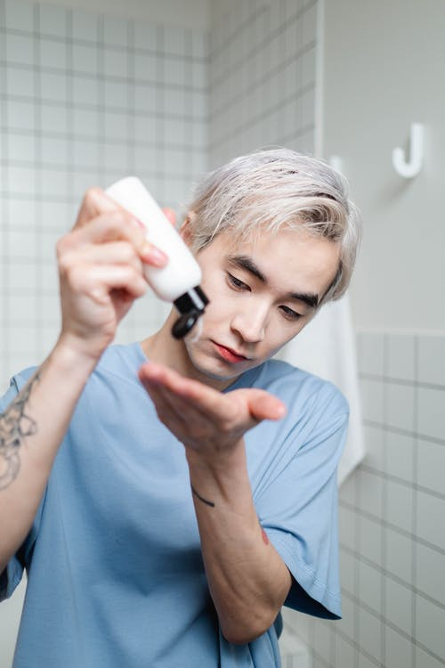 Man in Blue Crew Neck Shirt Holding A Bottle Of Beauty Product