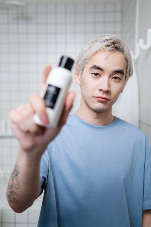Man in Blue Crew Neck Shirt Holding White and Black Bottle