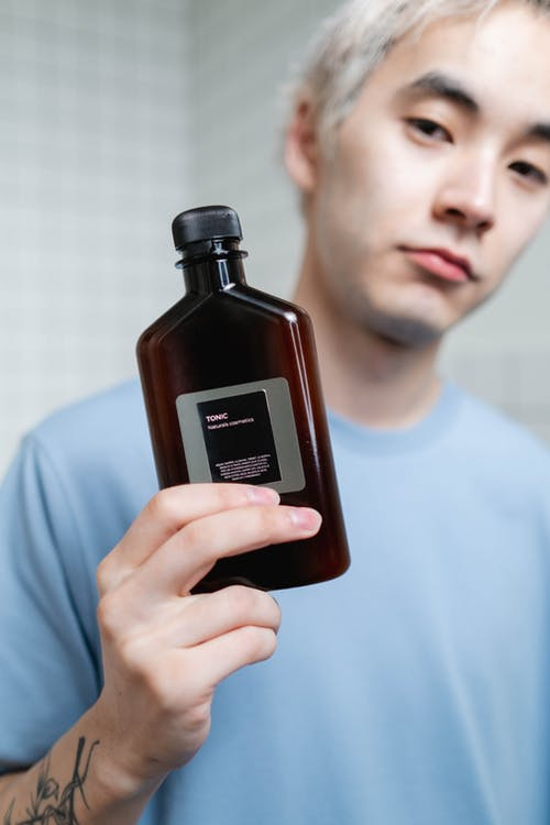 Man in Blue Crew Neck Shirt Holding A Brown Bottle