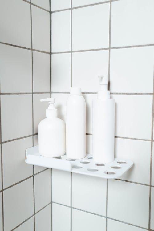 White Plastic Bottles on White Ceramic Wall Tiles
