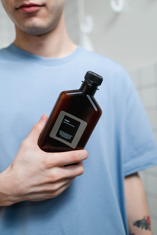 Man in Blue Crew Neck Shirt Holding Brown Bottle