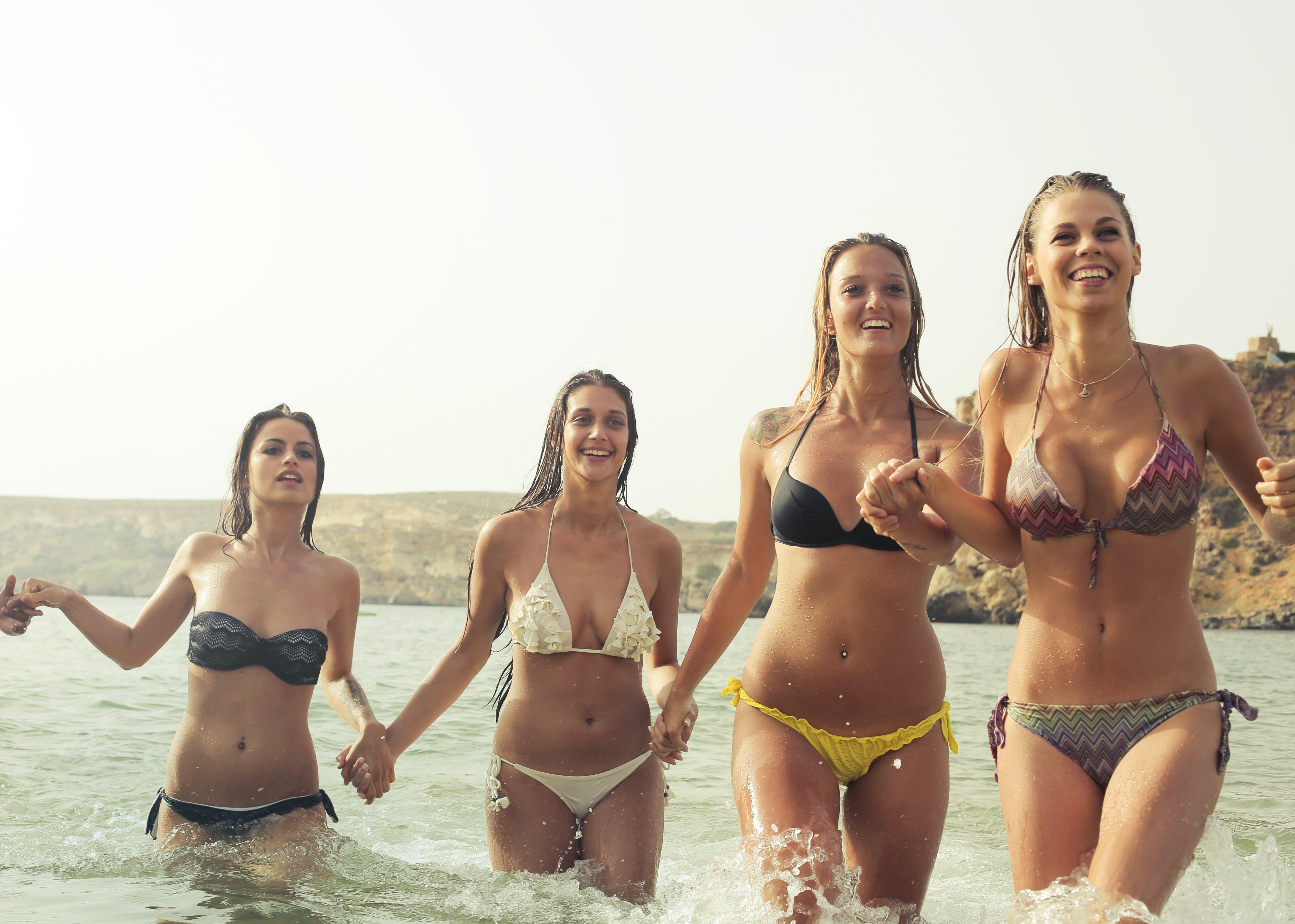 Group of Woman Wearing Bikini on Body of Water