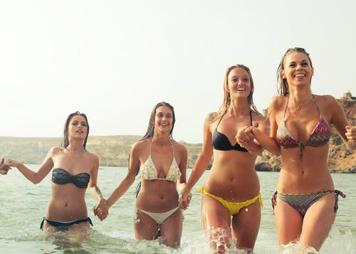 Group of Women Wearing Bikini on Body of Water
