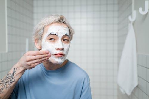 Man in Blue Crew Neck Shirt Applying Cream On His Face