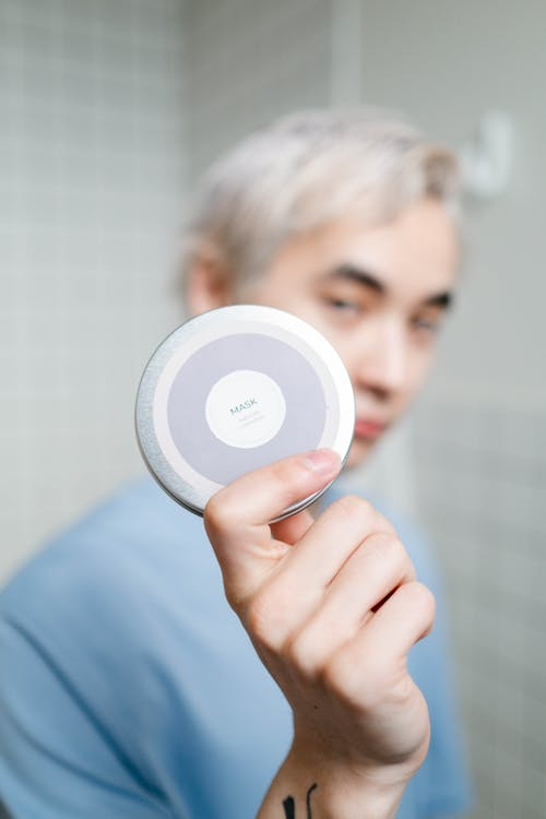 Man Holding A Cosmetic Mask In Round Container