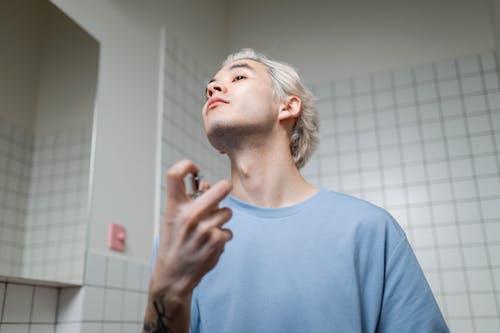 Man in Blue Crew Neck T-shirt Applying Perfume
