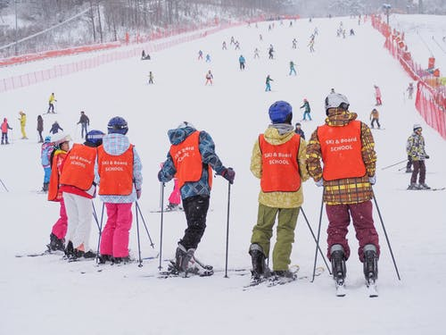People in Red Jacket and Pants on Snow Covered Ground