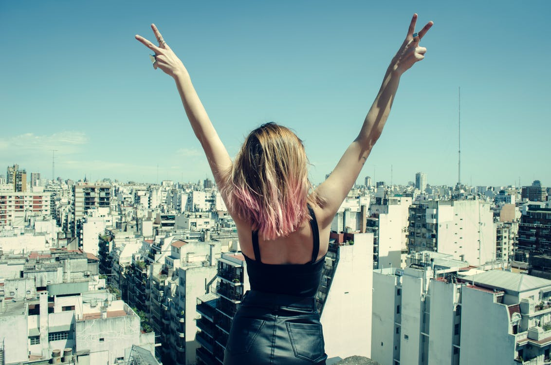 Woman Standing on Rooftop Putting Hands in the Air Under Clear Sky